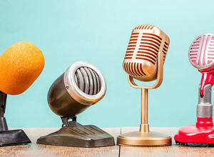 Bright retro microphones stand against a blue tone background